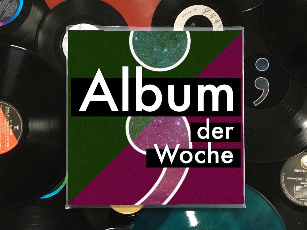 Eine Schallplatten-Hülle mit der Aufschrift Album der Woche liegt auf losen Schallplatten.